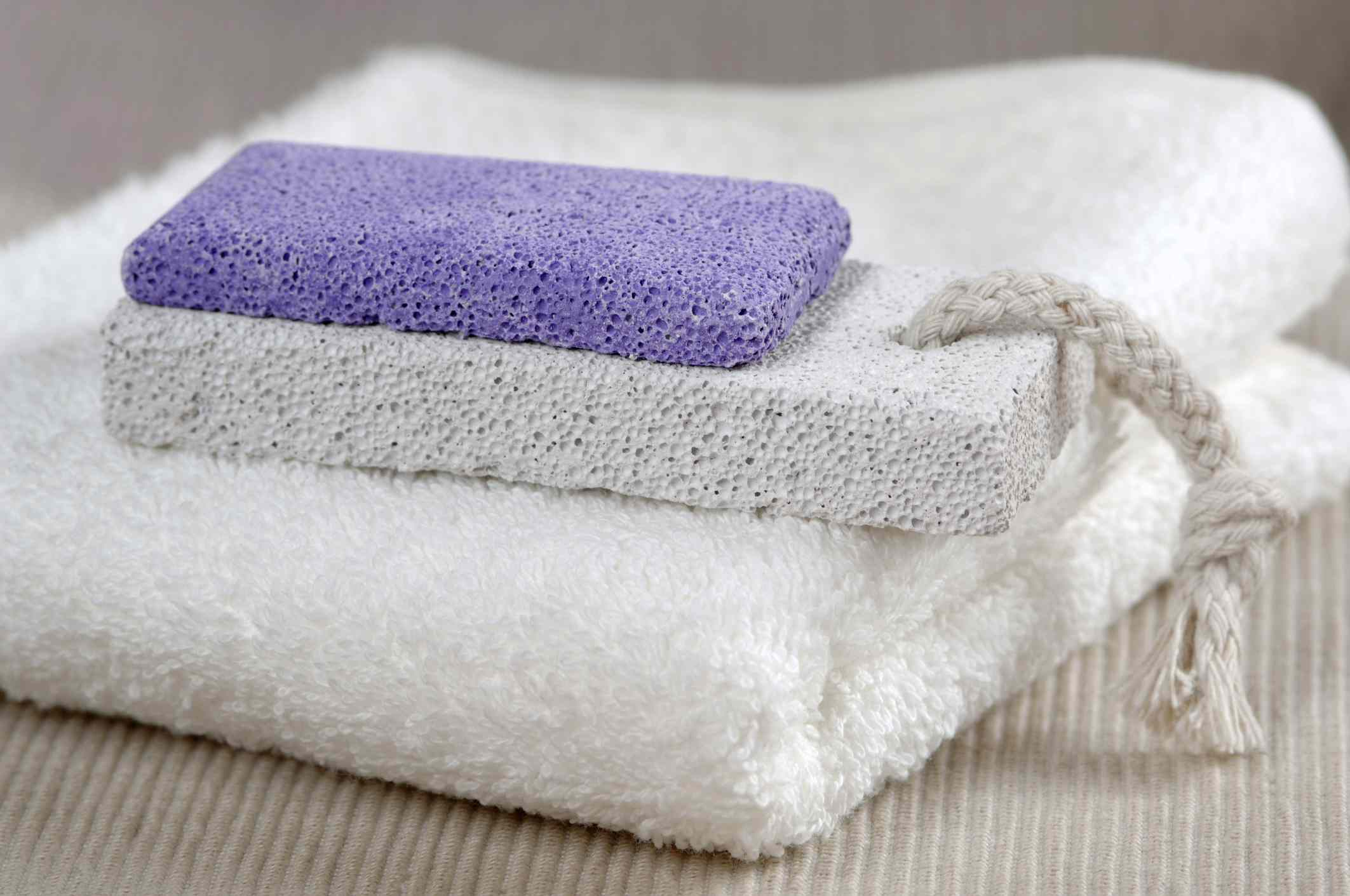 two pumice stones sit atop a towel.