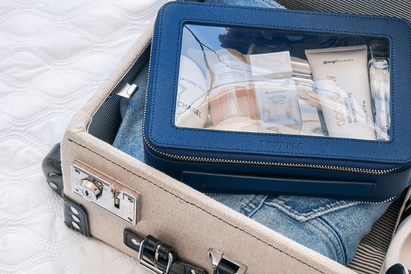 clear makeup bag packed in a suitcase