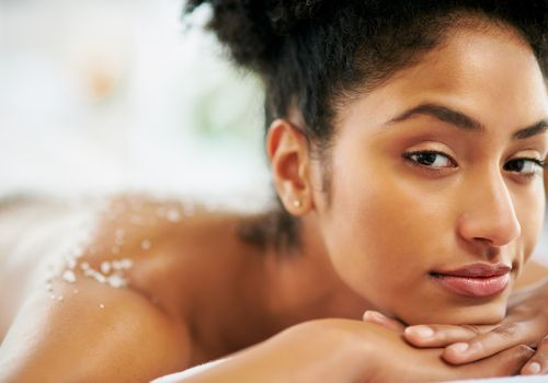 Black woman laying down with an exfoliating scrub on shoulders