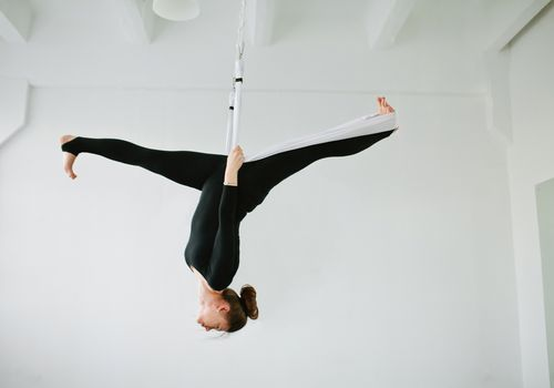 woman doing aerial yoga in white studio