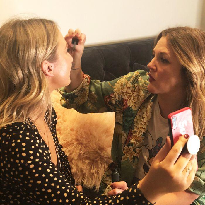 Drew Barrymore applying makeup to writer Chloe Burcham's face
