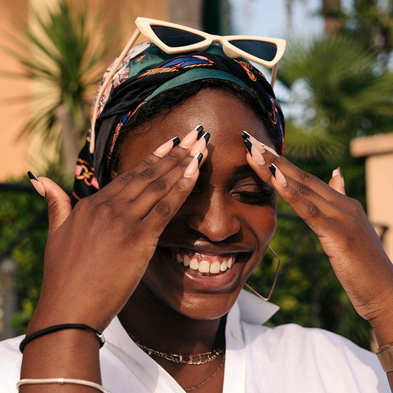 black femme hiding face from sun