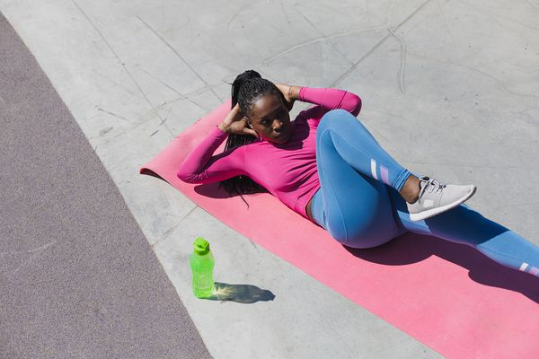 Woman doing abdominal exercises on a yoga mat outdoors.