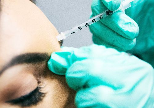 woman getting needle injected into her forehead