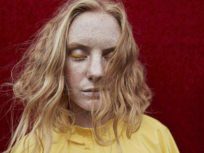 Woman with strawberry blonde hair, wearing a yellow shirt