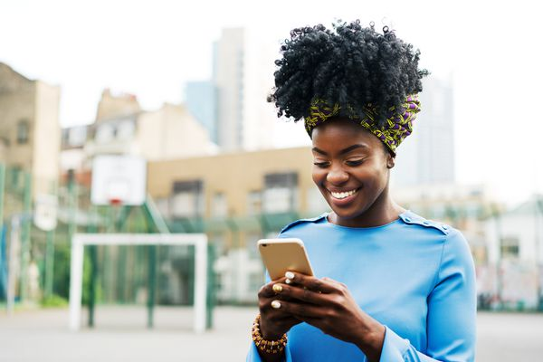 Woman looking down at her cell phone outside