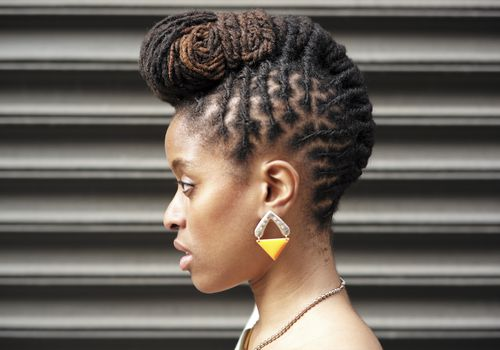 African American woman with braids near metal wall