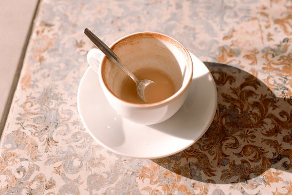 an almost empty cup of coffee on a tile counter with a small spoon in the cup