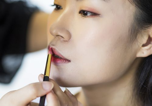 Makeup artist applying lipstick
