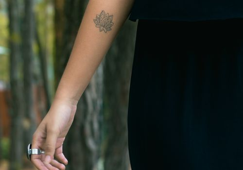 woman with lotus flower tattoo on arm