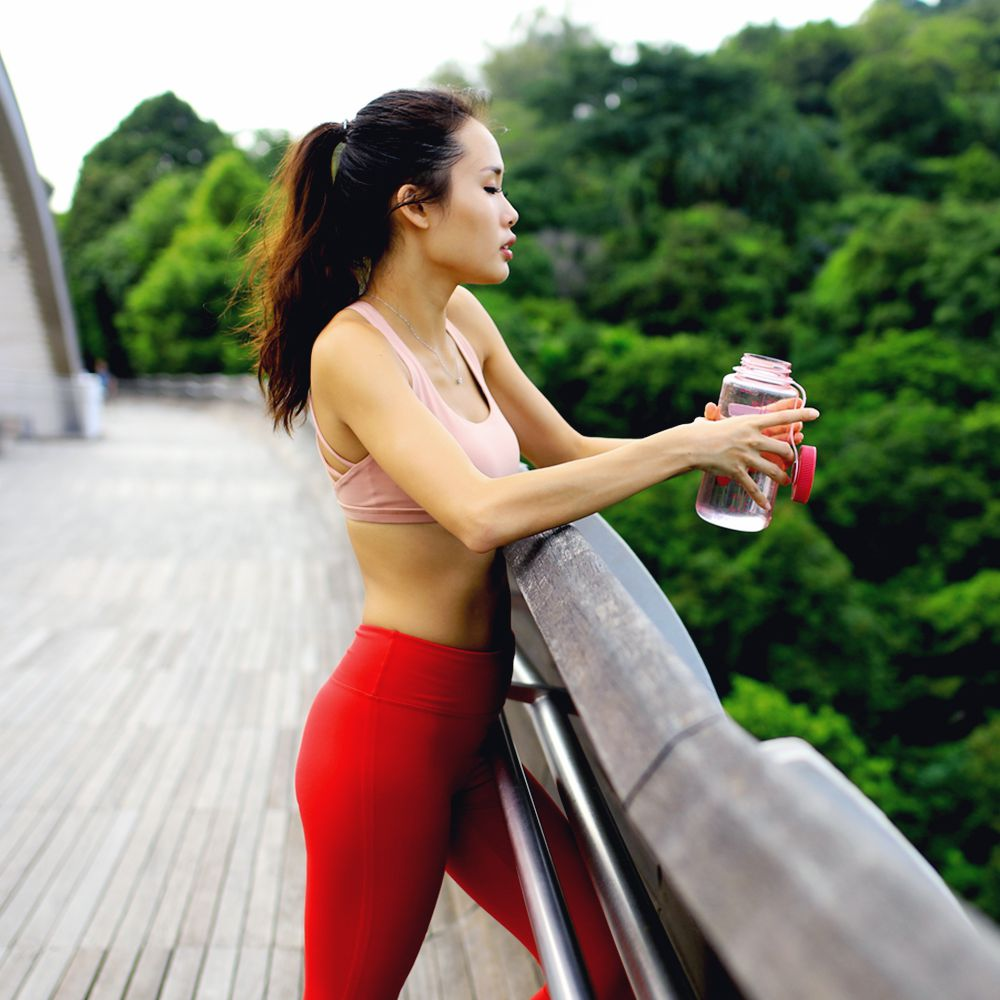 person drinking water in the middle of run