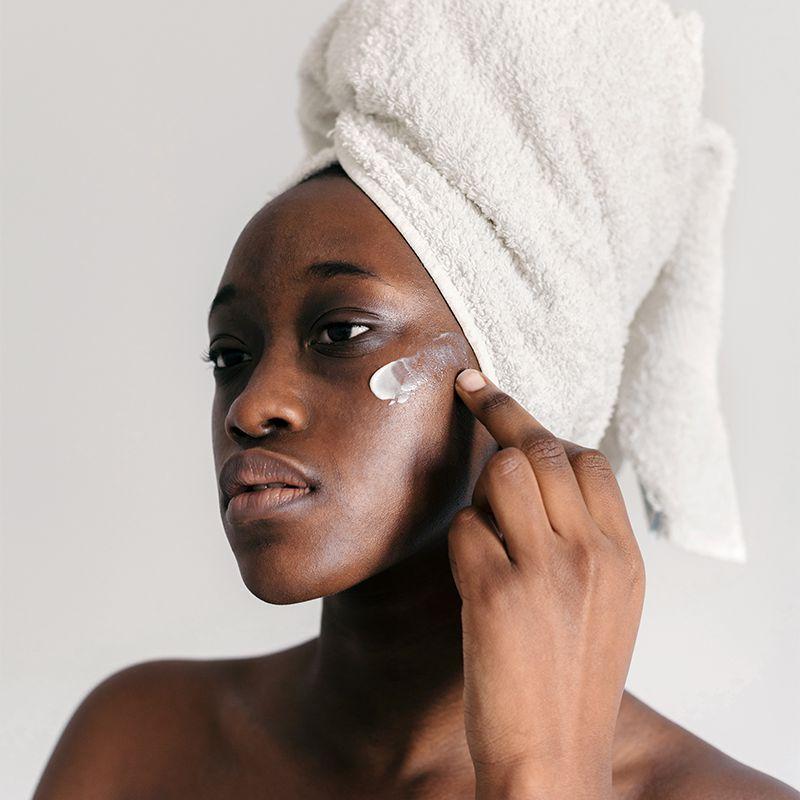 black femme applying face lotion
