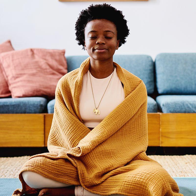 black femme meditating on yoga mat