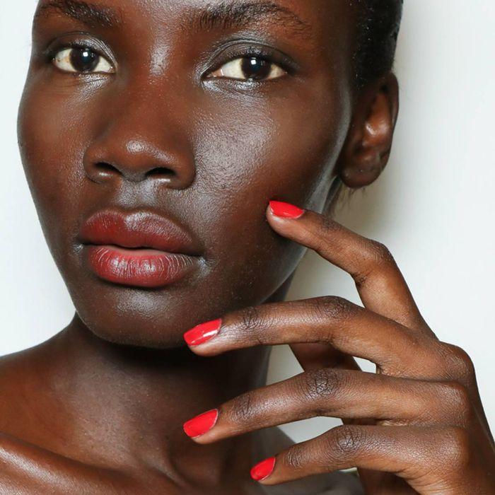Model wearing vibrant red nail polish