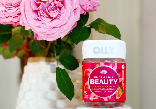 olly undeniable beauty gummy vitamins next to pink flowers