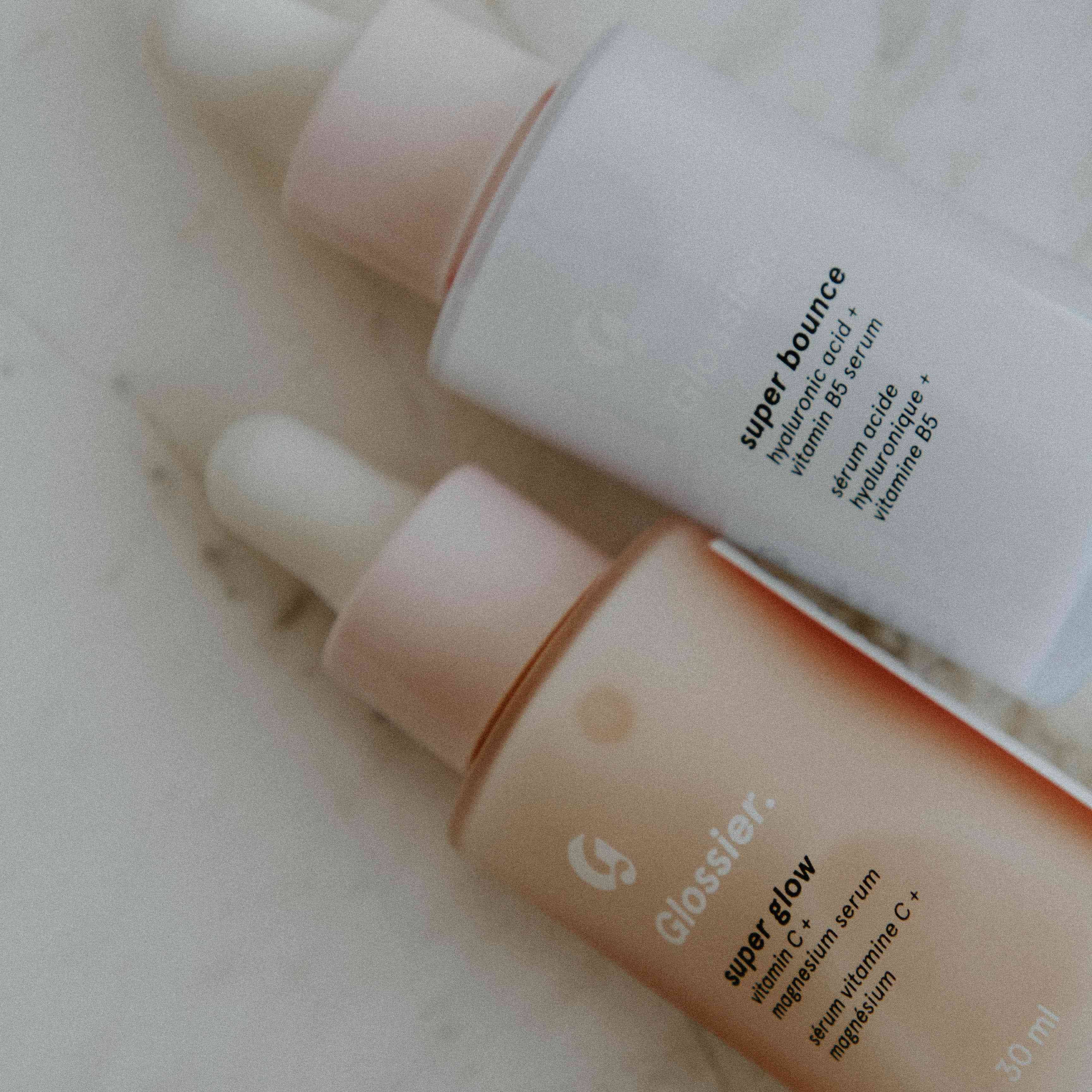Glossier super glow and super bounce serums on a marble backgrouns