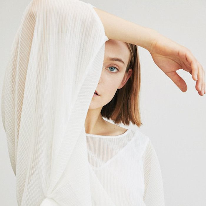 A woman wearing a white shirt holding her elbow to her forehead