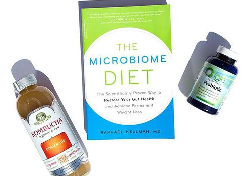 Bottle of Kombucha, The Microbiome Diet book, and a bottle of probiotic supplements against white background