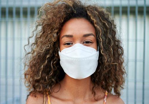 Woman with curly hair and mask