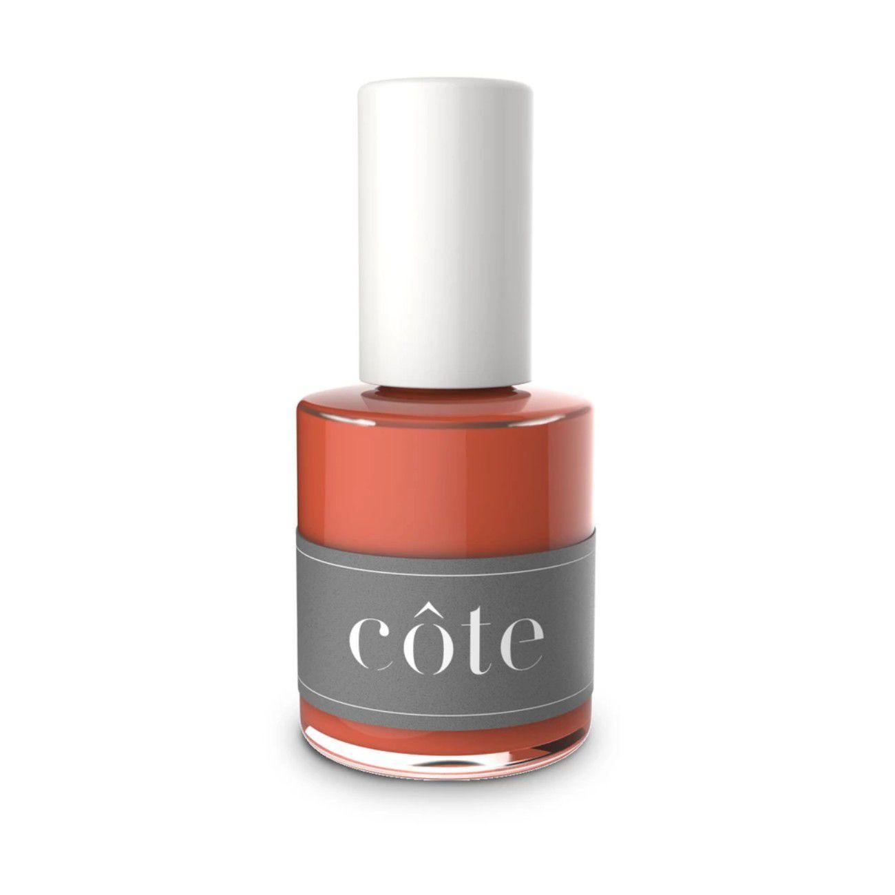 Bottle of burnt orange nail polish on a white background.