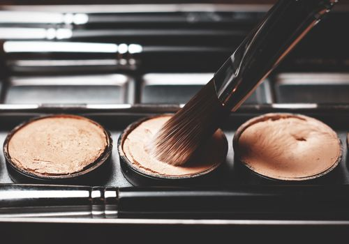Pots of concealer and a makeup brush