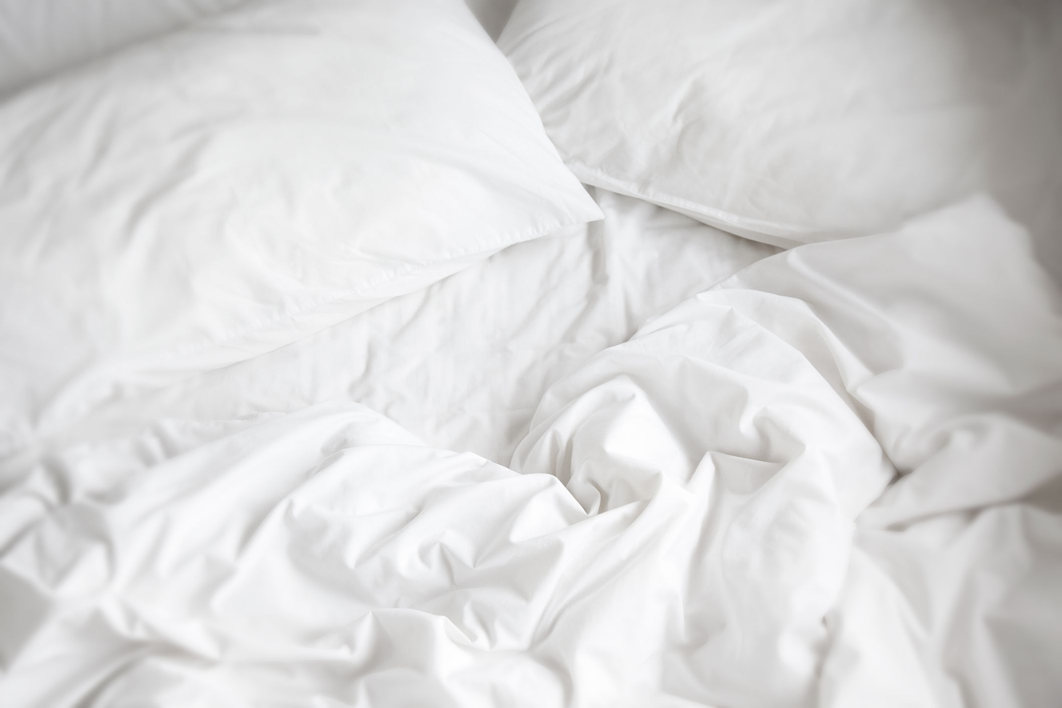 white bed sheets, pillows, and comforter.