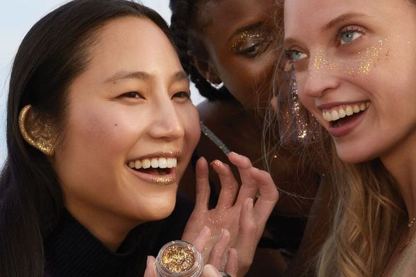 three women smiling with glitter makeup