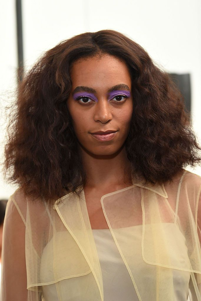 Solange mid-length curly brushed hairstyle with purple eyeshadow