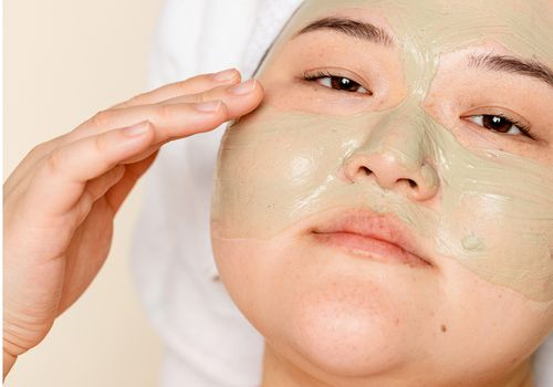 person applying clay skincare mask