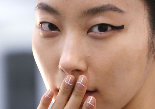 Asian woman with hand over her mouth showing off manicure.