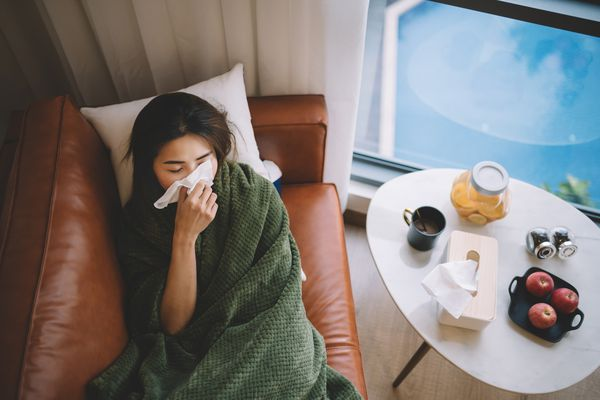 Asian woman at home sick on her couch