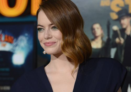 emma stone on a red carpet with rust hair