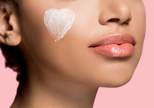 girl with heart-shaped cream on her cheek