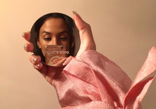 """woman looking into mirror that says """"you look good"""""""