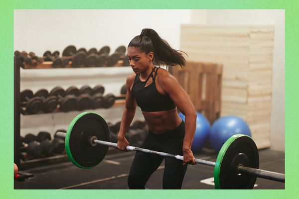 Woman weight lifting a barbell in a gym.