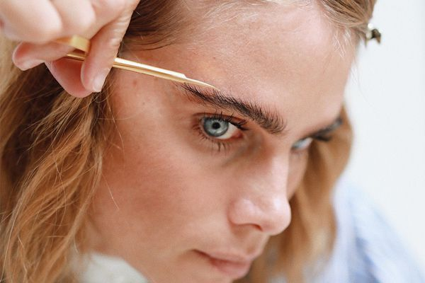 woman trimming eyebrows
