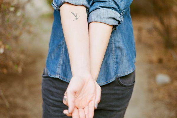 Person in a denim shirt showing a bird tattoo on their inner arm