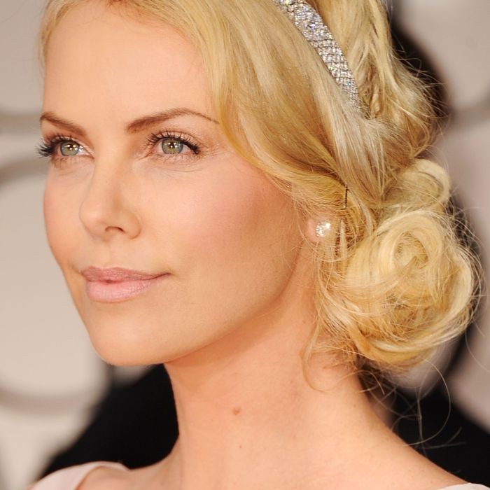 Charlize Theron with loosely curled low-bun and bedazzled headband