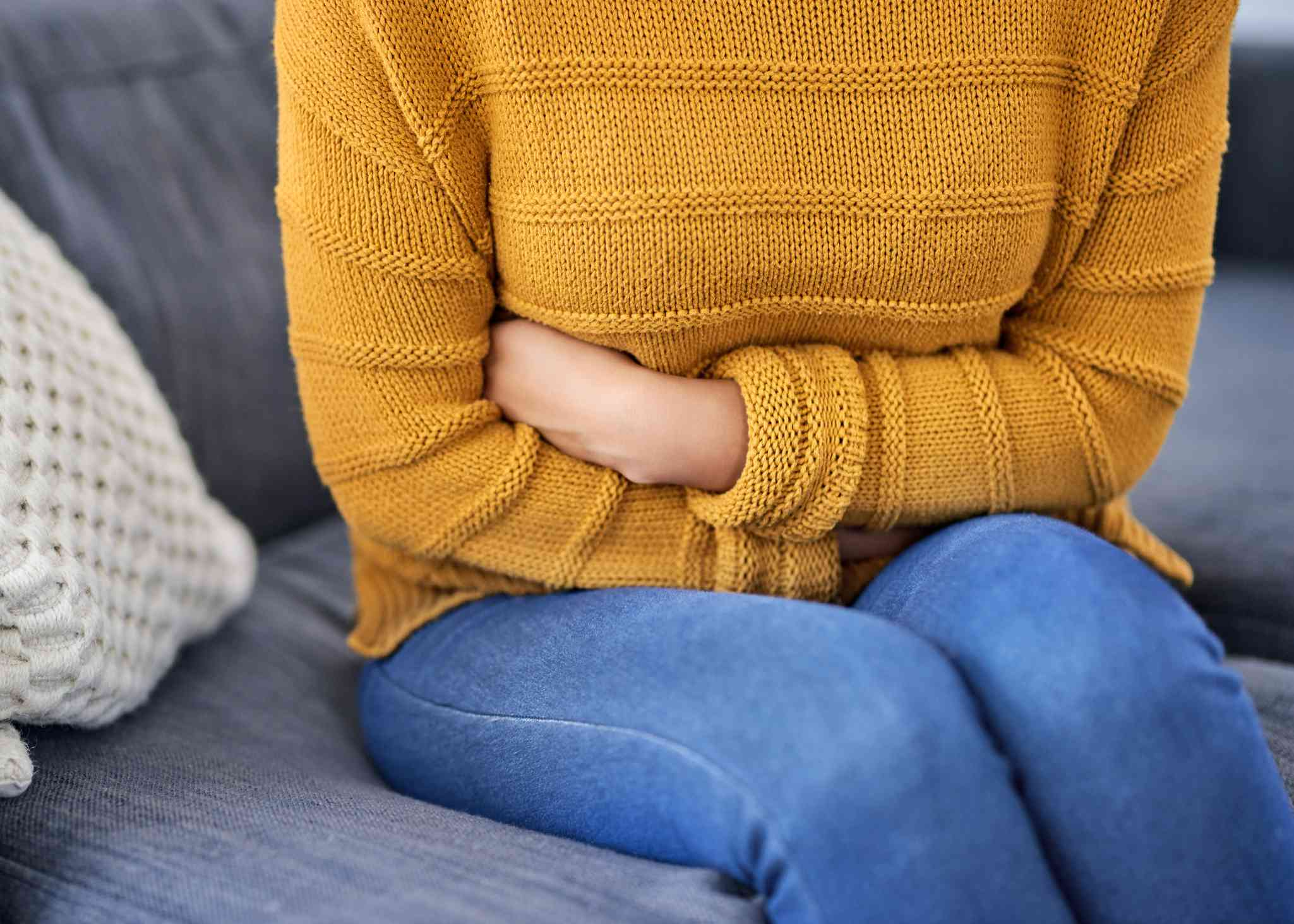 Individual in yellow sweater clutches stomach