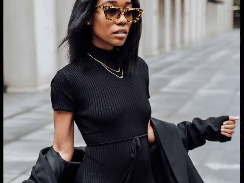 woman wearing an all-black outfit with silk hair and sunglasses