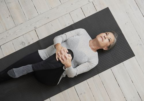 Woman laying on her back on a Pilates mat
