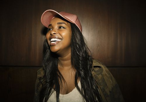 Young black woman with curly hair and a pink satin baseball hat on