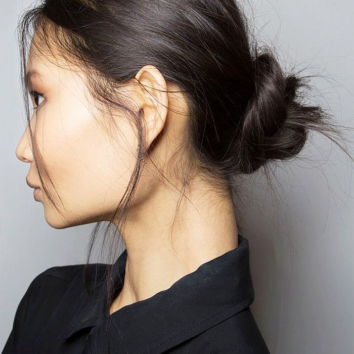 Woman with dark hair styled in a twisted bun