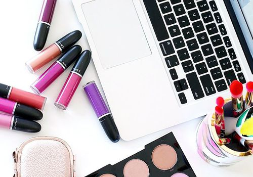 Laptop with liquid lipstick and makeup brushes