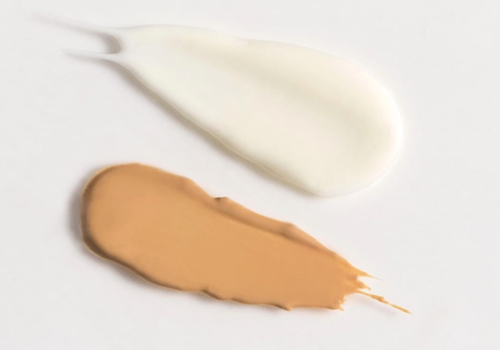two swatches of sunscreen on white background