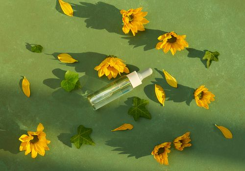 skin care health beauty essential oil on tennis court with sunflowers