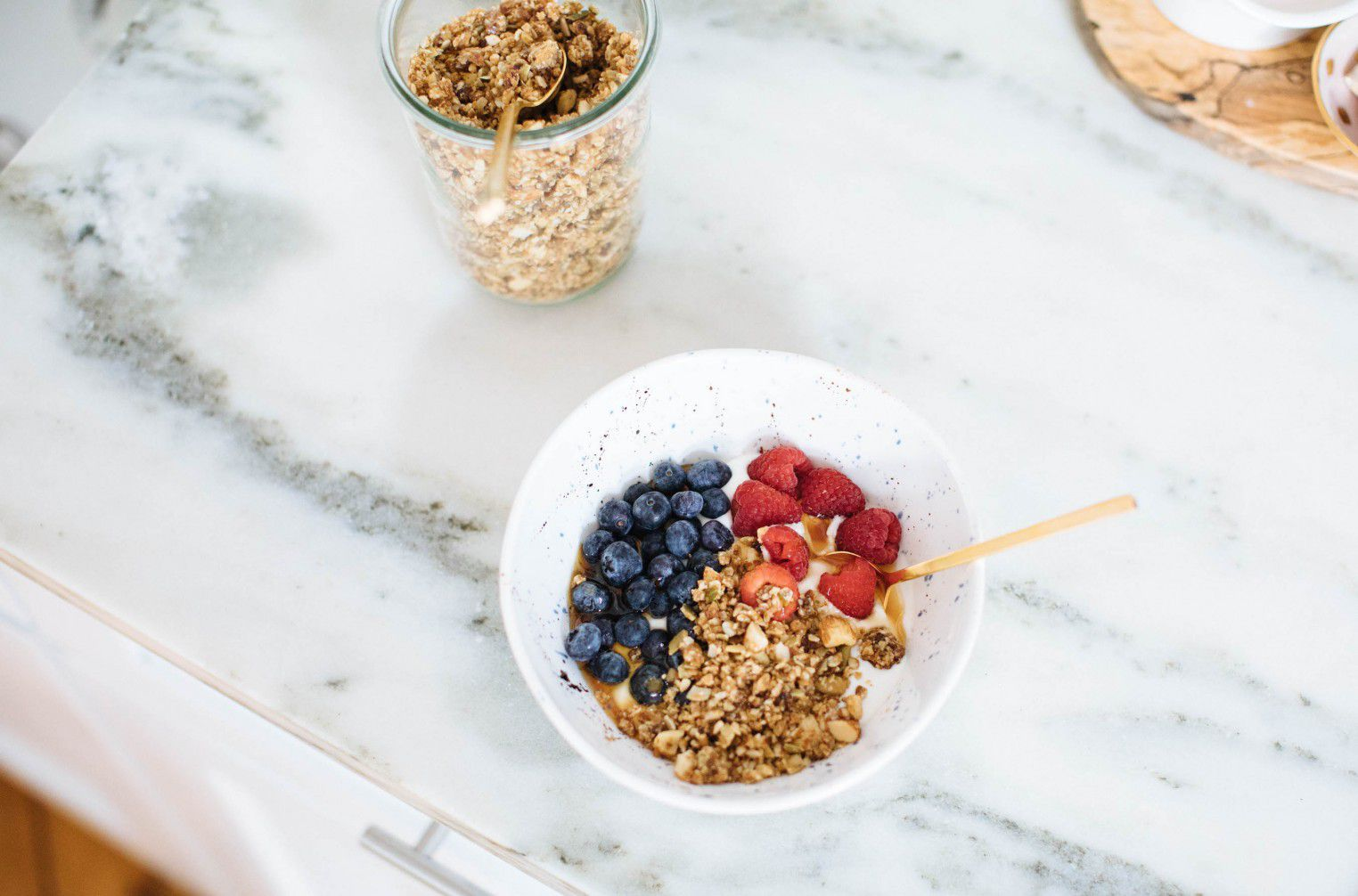 a jar of granola sits on a table or countertop beside a bowl of yogurt topped with granola and berries.