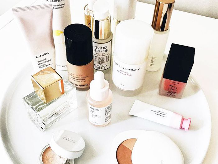 Different beauty products on a white circle-shaped tray