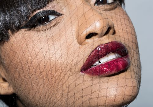 Young black woman with awesome eyeliner and a net over her face