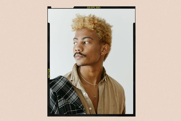 man with blond curly hair with beige border